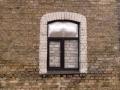 Visai savdabīga kompozīcija - brūns plastmasas pakešu logs, aiz tā ķieģeļu mūris. Mūkusalas 11, Rīga